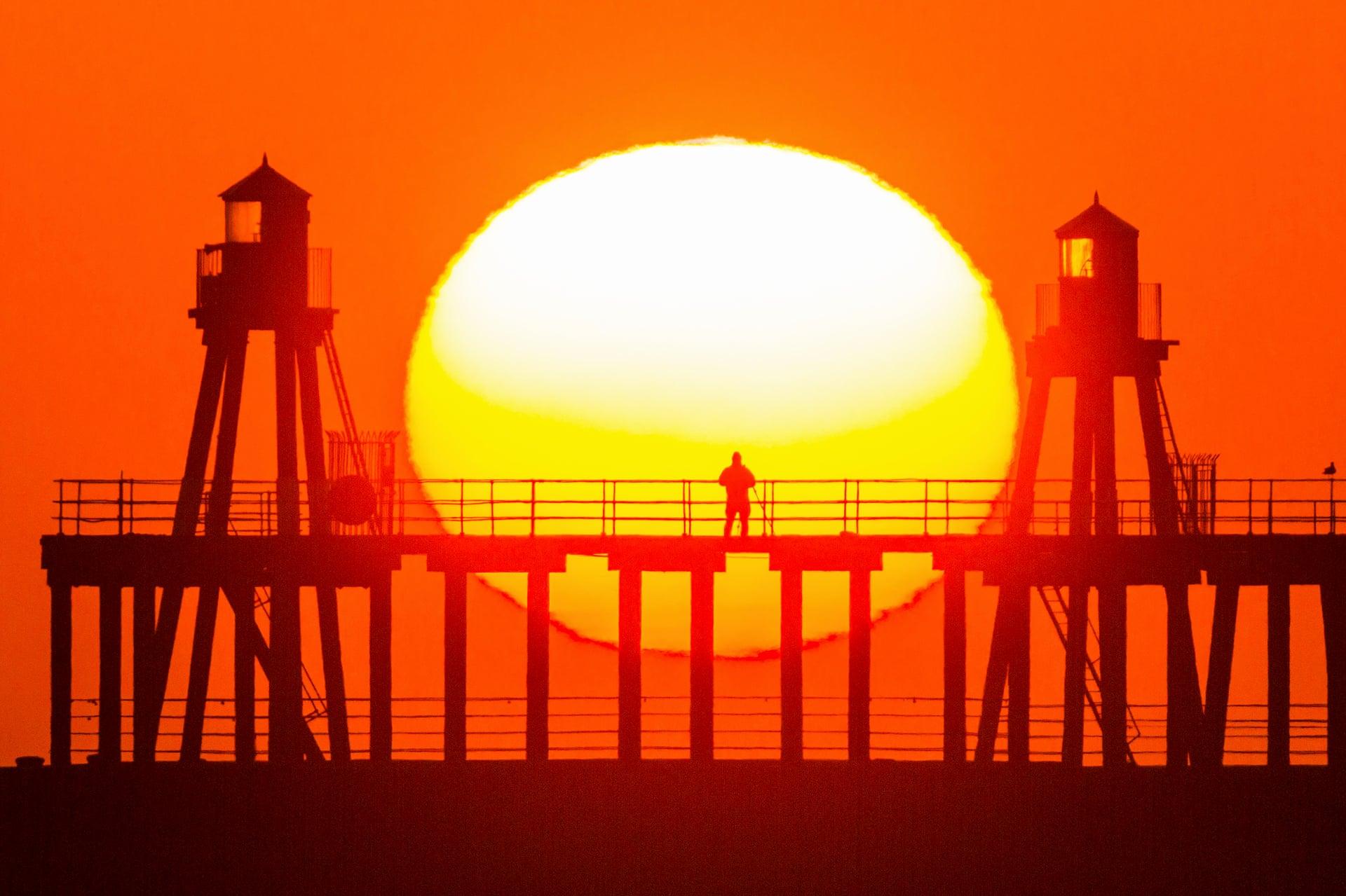 Un uomo da solo sul molo a guardare l'alba sulla costa del North Yorkshire