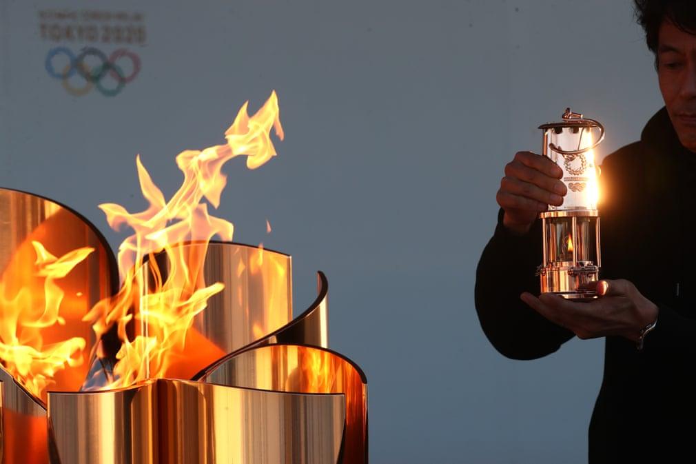 Un membro dello staff conserva la fiamma olimpica
