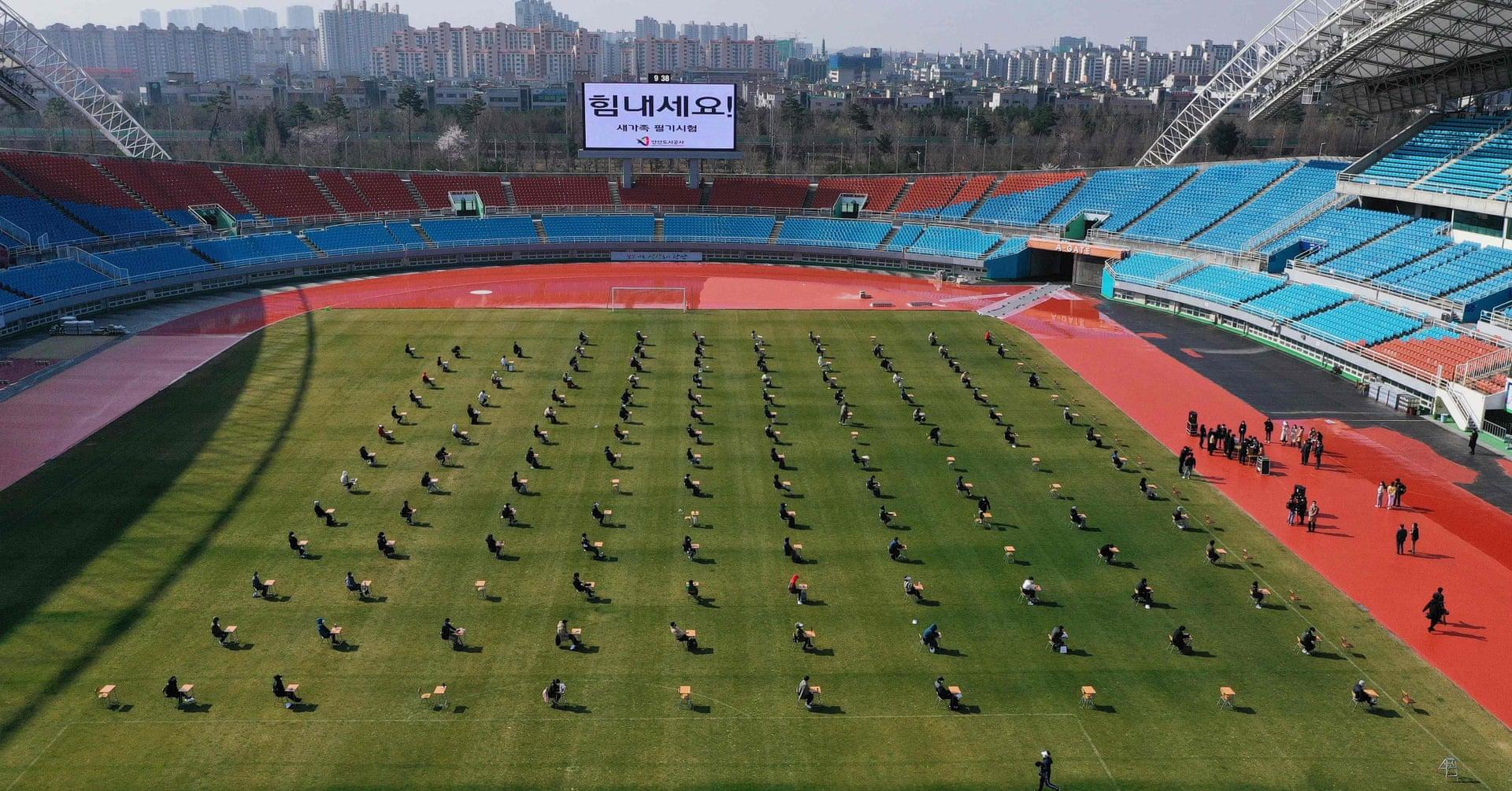 I candidati sostengono un esame scritto su un campo di calcio durante un test di reclutamento